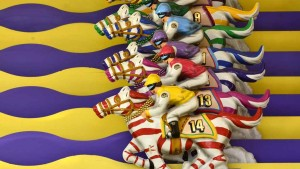 The horse race begins when players roll balls in holes.