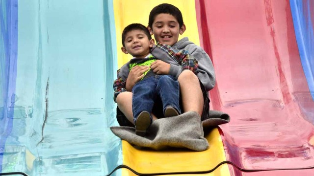 Kids 12 and younger get into the County fair free on Tuesdays. Family members enjoy the slide.