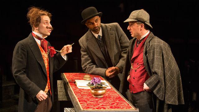 "Blake Segal (left) as Castilian Desk Clerk, Usman Ally as Doctor Watson, and Euan Morton as Sherlock Holmes in Ken Ludwig's ""Baskerville: A Sherlock Holmes Mystery"" at The Old Globe. Photo by Jim Cox"