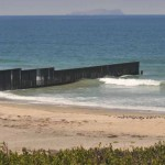 The fence into the ocean shows the U.S.-Mexican border.