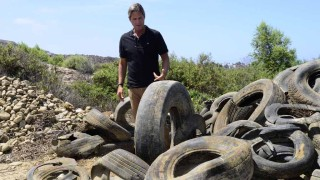 Imperial Beach Mayor Serge Dedina shows a pile of tires pulled from the Tijuana River basin. New state money will help relieve the problem.