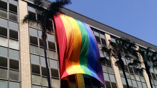 The LGBT Pride flag ripples in the wind in front of the state office building in downtown San Diego. Photo by Chris Jennewein