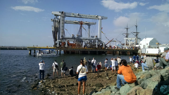 Spectators scrambled down rocks at Bayside Park to watch the San Salvador touch the water. Photo by Chris Jennewein