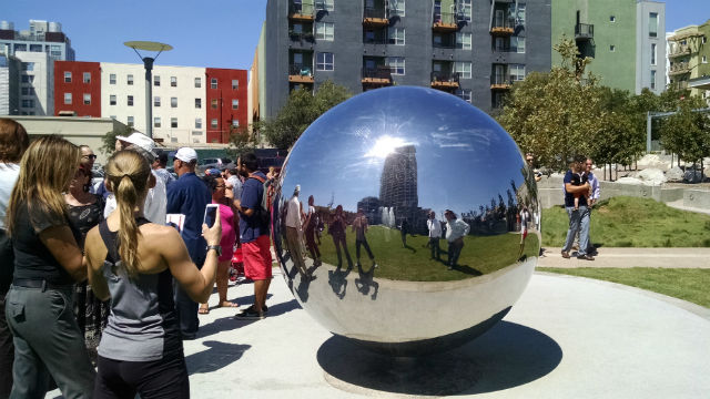 The Pinnacle in the Park tower is reflected in artwork at Fault Link Park. Photo by Chris Jennewein