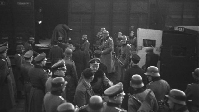 Nazi SS troops load Jews into boxcars at Marseille, France, in January 1943. Photo via Wikimedia Commons