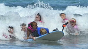 A team of Richochet helpers push the surfboard into a wave. Photo by Chris Stone