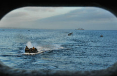 Amphibious assault vehicles prepare to enter the well deck of the amphibious transport dock ship USS New Orleans during Exercise Dawn Blitz. Navy photo