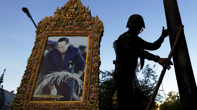A soldier climbs a barricade in front of a picture of Thailand King Bhumibol Adulyadej. REUTERS/Damir Sagolij