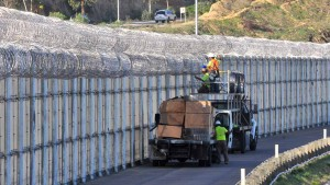 Workers install additional wiring on the double fence between the U.S. and Mexico. Photo by Chris Stone