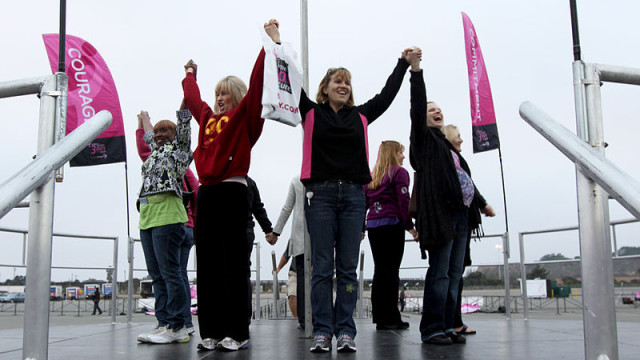 "Eight breast cancer survivors carry eight flags  representing courage, commitment, love, hope, patience, optimism, belief, and healing, during the ""Susan G. Komen 3-Day for the Cure"" walk. Image from Wikimedia Commons."