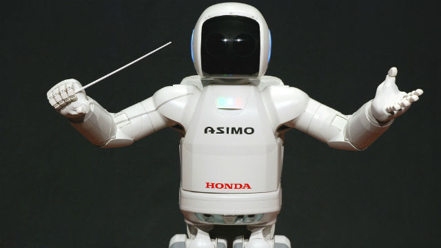 Honda's humanoid robot ASIMO conducting an orchestra in 2008. Photo by Vanillase via Wikimedia Commons