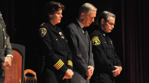 Police Chief Shelley Zimmerman, former Gov. Pete Wilson and law enforcement chaplain Herb Smith bow their heads during invocation. Photo by Chris Stone