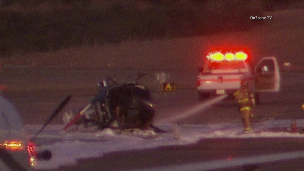 Firefighting vehicles surround the wrecked helicopter on the tarmac at Palomar Airport. Courtesy OnScene.TV