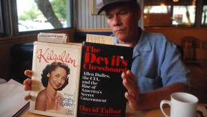 Gene Bryan holds two books his team is studying for clues to Dorothy Kilgallen death, even though the biography is flawed in their minds. Photo by Ken Stone
