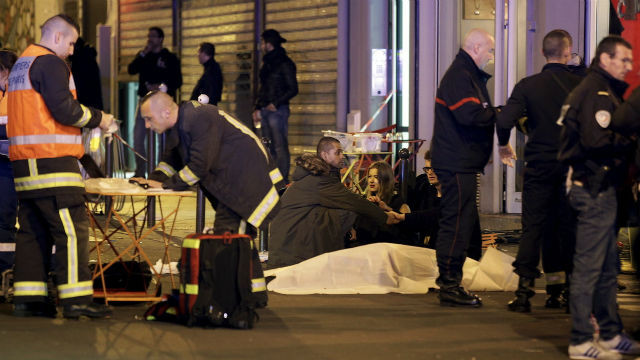 Rescue workers with covered bodies in Paris after the coordinated attacks. REUTERS/Phillippie Wojazer