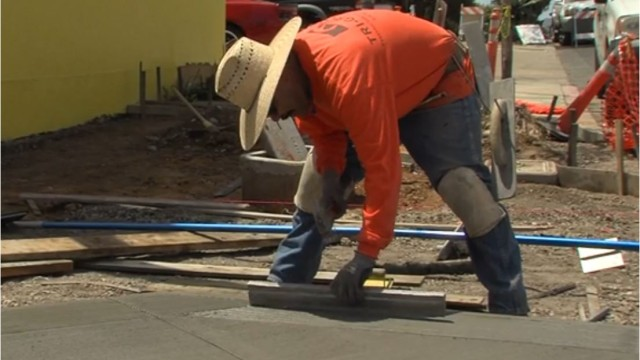 A construction worker levels concrete for a new San Diego sidewalk. Image courtesy mayor's office