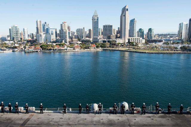 Sailors man the rail as the amphibious assault ship USS Essex passes downtown San Diego. Navy photo