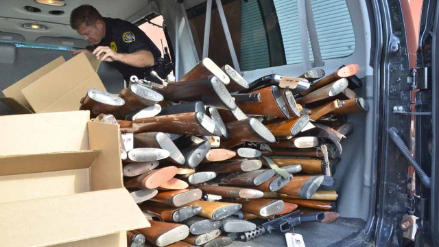 About 230 weapons were loaded into a police van after a buyback event. Photo by Chris Stone