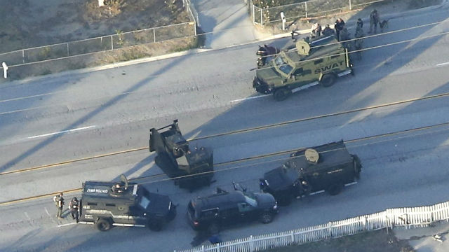 Police vehicles surround the black SUV in which the suspects were killed. Reuters photo