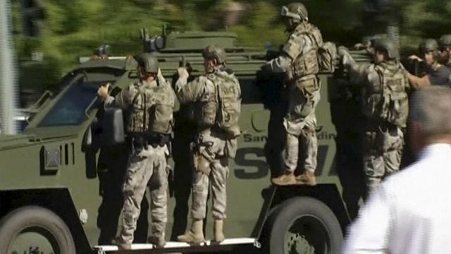 San Bernardino County Sheriff's SWAT team members ride an armored vehicle near the shooting. Reuters photo