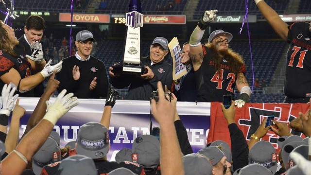 San Diego State football coach holding the conference championship trophy. This is the Aztecs' 20th conference title. Photo courtesy of San Diego State Athletics