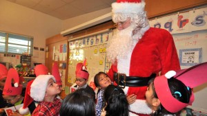Children at Burbank Elementary School in Logan Heights hug and tell Santa what they want for Christmas. Photo by Chris Stone