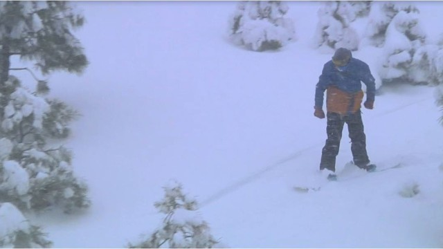 A man snowboarding amid falling snow at the Mountain High resort north of Ontario. Courtesy of Mountain High