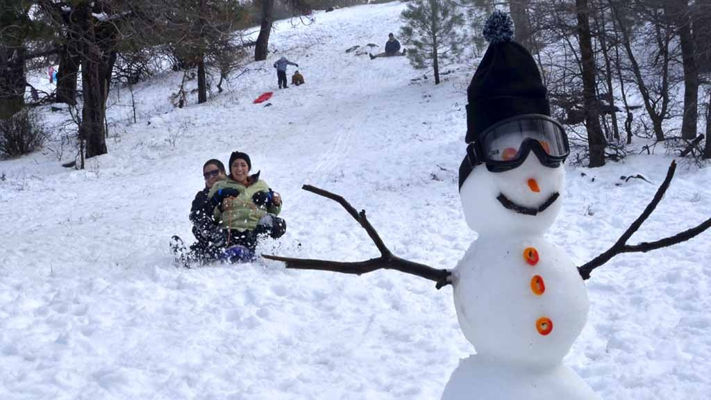 Snow people dotted the mountainsides as San Diegans slid down the snow-covered hills last year. Photo by Chris Stone