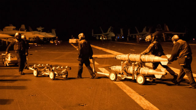 Sailors preparing to load bombs onto waiting aircraft on the flight deck of the USS Harry Truman in the Arabian Gulf. Navy photo