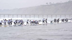 Surfers at La Jolla Shores make one of 16 attempts at Guinness World Record for most riding a single wave. Photo by Chris Stone