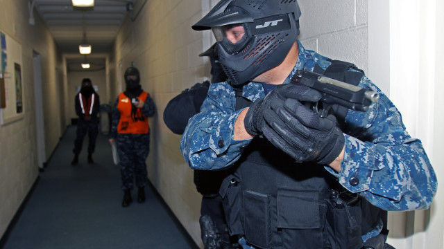150210-N-IM823-044 FALLON, Nev. (Feb. 10, 2015) Master-at-Arms 2nd Class Shane Miles communicates with Master-at-Arms Ryan Young as they clear a passageway during an active shooter exercise at Naval Air Station Fallon during the Navy-wide force protection exercise Solid Curtain-Citadel Shield 2015. (U.S. Navy photo by Mass Communication Specialist 1st Class Joseph R. Vincent/Released)