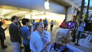 As many as 30 people gathered outside the Apple store in Fashion Valley to support the company. Photo by Chris Stone