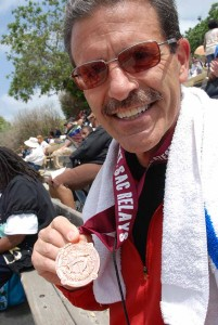Greg Pizza of Vista and the Orange County-based Southern California Striders shows off a medal won at a recent Mt. SAC Relays in Walnut. Photo by Ken Stone