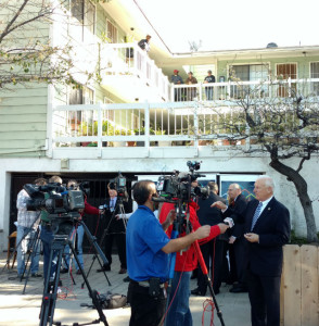 Ron Roberts is interviewed as residents of one of Chris Blatt's apartments watch. Photo by Chris Jennewein