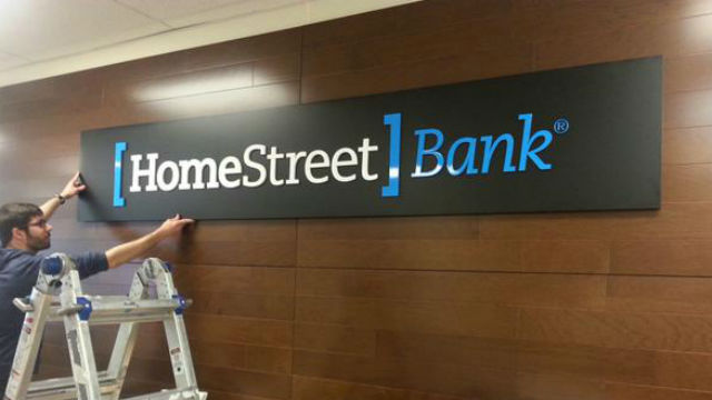A workman installs a HomeStreet Bank sign at a branch. Courtesy HomeStreet Bank