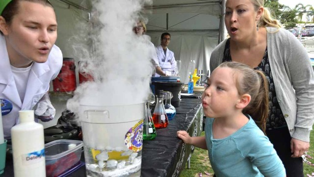 A young girl and her mother blow on the liquid nitrogen vapor at the San Diego Festival of Science and Engineering. Photo by Chris Stone