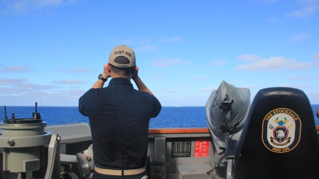 USS Stockdale's officer of the deck scans the horizon for other surface vessels during a routine patrol in the South China Sea. Navy photo