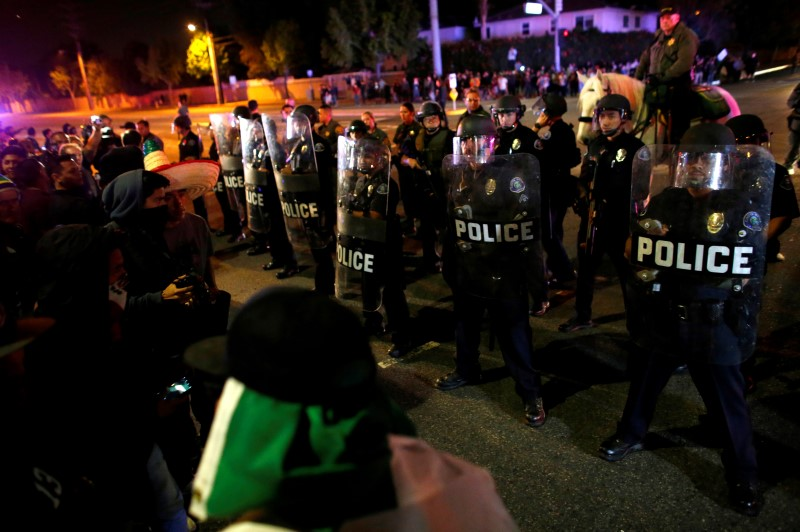 Police in riot gear arrive to break up a demonstration outside Republican U.S. presidential candidate Donald Trump's campaign rally in Costa Mesa, California, April 28, 2016. REUTERS/Mike Blake