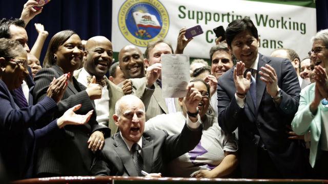 Gov. Jerry Brown signs $15 minimum wage law in Los Angeles. Courtesy SEIU California