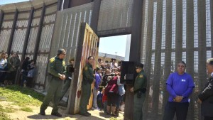 Border Patrol agents stay near the border gate as families hug just inside the Mexican side of the fence. Photo by Chris Stone