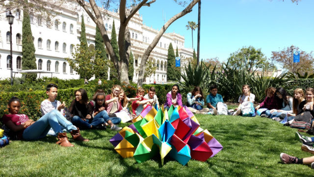 Students from High Tech Middle surround their finished origami sculpture. Photo by Chris Jennewein