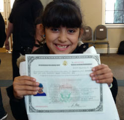 One of the new citizens holds her certificate.