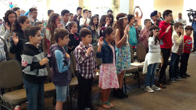 The children take the oath of allegiance at the New Americans Museum. Photo by Chris Jennewein