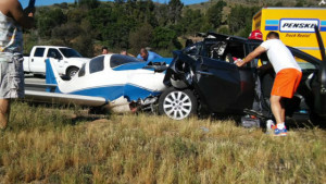 The wrecked plane and damaged car on Interstate 15. Photo via Twitter feed of T-Dawg Jenkins @gohead287