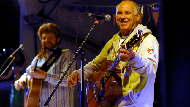 "MIDDLE EASTERN PORT (Jan. 28, 2008) Recording artists Jimmy Buffett, right, and Mac Macnally, a member of the ""Coral Reefer Band,"" perform a USO concert for the Sailors of the Nimitz-class aircraft carrier USS Harry S. Truman (CVN 75) during a recent port visit in the Middle East. Truman and embarked Carrier Air Wing (CVW) 3 are underway on a scheduled deployment supporting Operations Iraqi Freedom, Enduring Freedom and maritime security operations. U.S. Navy photo by Chief Mass Communication Specialist Michael W. Pendergrass (Released). U.S. Navy photo by Chief Mass Communication Specialist Michael W. Pendergrass [Public domain], via Wikimedia Commons"