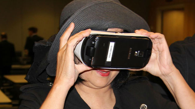 A woman tests virtual reality goggles.