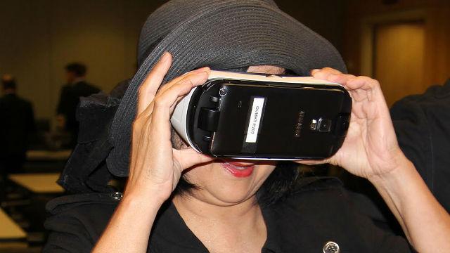 A woman tests virtual reality goggles.