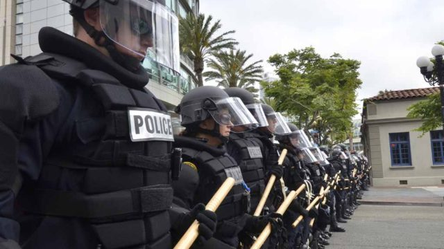 Police line up before advancing on the protesters in downtown San Diego. Photo by Chris Stone