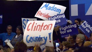 Supporters held up signs for Hillary Clinton at a speech by former President Bill Clinton. Photo by Chris Stone