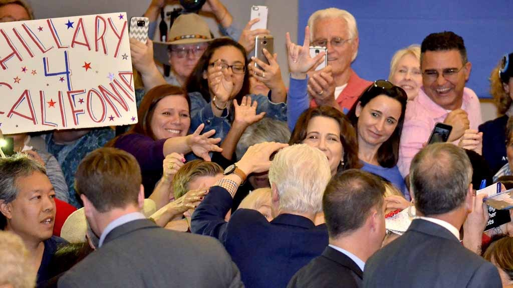 Well-wishers reach out to former President Bill Clinton as he greets people along the rope line. Photo by Chris Stone